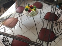 Glass top table with leather padded iron chairs